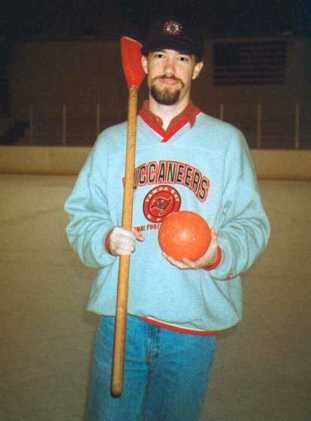 Jim Ellwanger holding a broomball stick